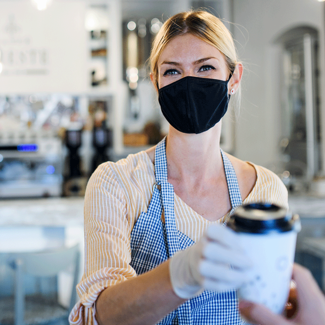 Photo of person in mask serving coffee
